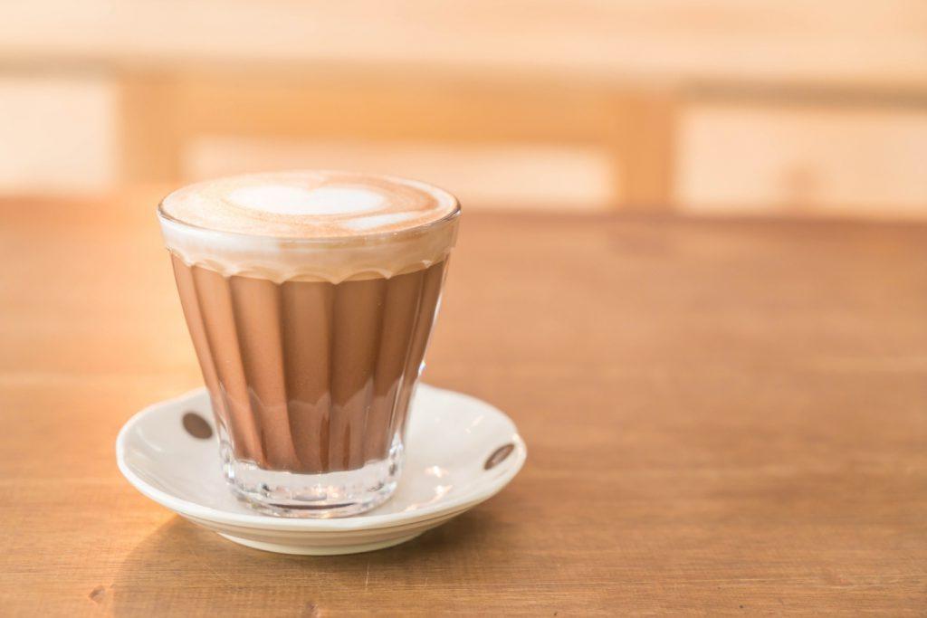 กาแฟมอคค่าร้อนในแก้วใส บนโต๊ะไม้